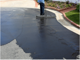 Man applying asphalt sealcoat.